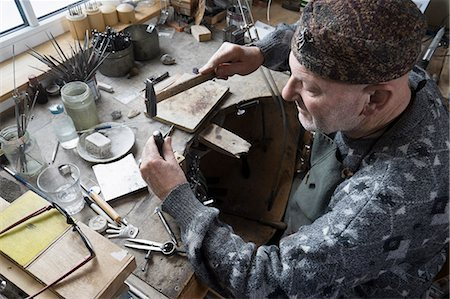 Senior male goldsmith hitting punches in workshop, Bavaria, Germany Stock Photo - Premium Royalty-Free, Code: 6121-08106900