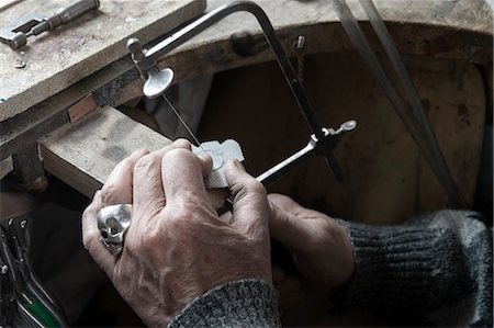 Senior goldsmith shaping crystal with hand saw in workshop, Bavaria, Germany Stock Photo - Premium Royalty-Free, Code: 6121-08106902