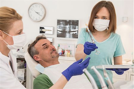 Female dentist examining patient with dental assistant, Munich, Bavaria, Germany Stock Photo - Premium Royalty-Free, Code: 6121-08228447