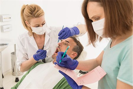 dentistry - Female dentist examining patient and dictating the findings to the assistant, Munich, Bavaria, Germany Stock Photo - Premium Royalty-Free, Code: 6121-08228454