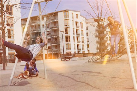 Friends swinging in a playground, Munich, Bavaria, Germany Stock Photo - Premium Royalty-Free, Code: 6121-08228518