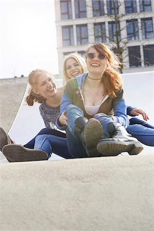 sole - Three friends sliding down slide in a playground, Munich, Bavaria, Germany Stock Photo - Premium Royalty-Free, Code: 6121-08228524
