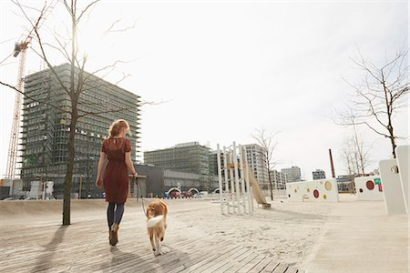 Rear view of a young woman walking in playground with dog, Munich, Bavaria, Germany Stock Photo - Premium Royalty-Free, Code: 6121-08228528