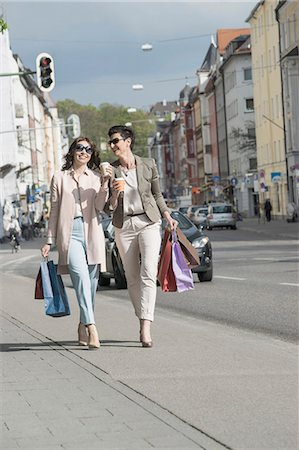 Two mature women shopping in the city with coffee, Bavaria, Germany Stock Photo - Premium Royalty-Free, Code: 6121-08228658