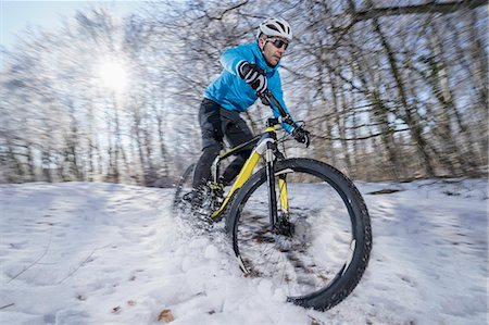 extreme terrain - Mountain biker riding a bike in a snowy forest, Bavaria, Germany Stock Photo - Premium Royalty-Free, Code: 6121-08228672