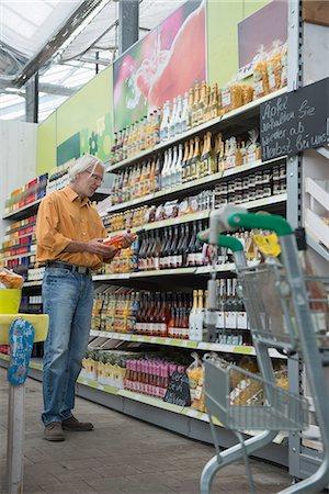 Customer reading label of wine bottle in supermarket, Augsburg, Bavaria, Germany Stock Photo - Premium Royalty-Free, Code: 6121-08228634