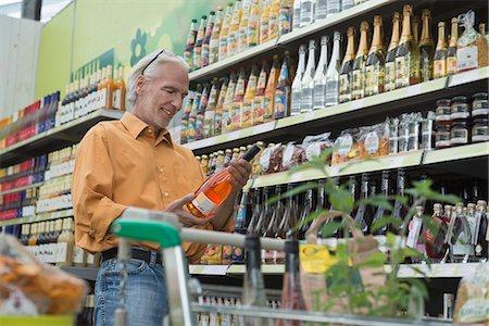 Customer reading label of wine bottle in supermarket, Augsburg, Bavaria, Germany Stock Photo - Premium Royalty-Free, Code: 6121-08228635