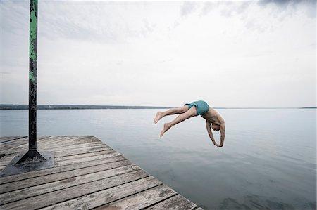 shirtless men - Mature man jumping into water on pier, Bavaria, Germany Stock Photo - Premium Royalty-Free, Code: 6121-08228744