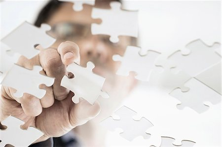 Businessman arranging jigsaw puzzle pieces, Bavaria, Germany Stock Photo - Premium Royalty-Free, Code: 6121-08228717