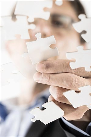 Businessman arranging jigsaw puzzle pieces, Bavaria, Germany Stock Photo - Premium Royalty-Free, Code: 6121-08228715