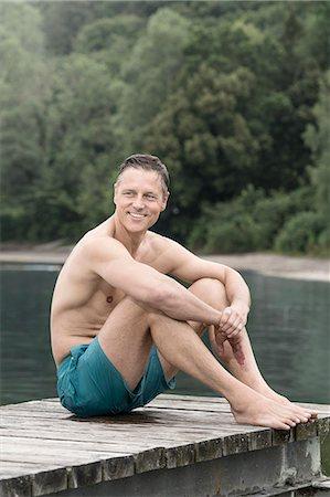 Mature man sitting on wooden pier, Bavaria, Germany Stock Photo - Premium Royalty-Free, Code: 6121-08228739