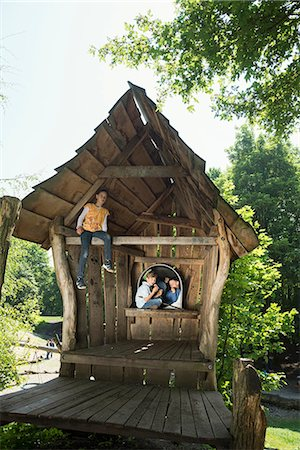 Two boys and a girl on a cottage in the adventure playground, Munich, Bavaria, Germany Stock Photo - Premium Royalty-Free, Code: 6121-08228841