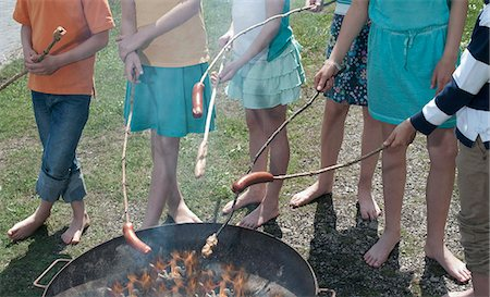 Group of friends preparing sausages on campfire, Bavaria, Germany Stock Photo - Premium Royalty-Free, Code: 6121-08228876