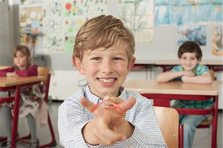preteen girls stretching - Schoolboy with a slingshot and smiling in classroom, Munich, Bavaria, Germany Stock Photo - Premium Royalty-Free, Code: 6121-08228890
