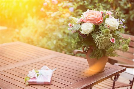 present wrapped close up - Gift with bouquet of flowers on table in garden, Munich, Bavaria, Germany Stock Photo - Premium Royalty-Free, Code: 6121-08361490