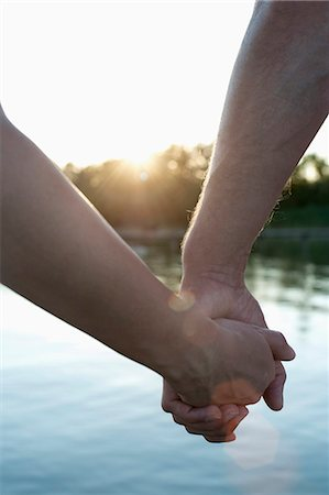 Close-up of couple in love holding hands during sunset, Bavaria, Germany Stock Photo - Premium Royalty-Free, Code: 6121-08361569