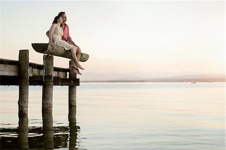 Mature couple sitting on pier looking over lake, Bavaria, Germany Stock Photo - Premium Royalty-Free, Code: 6121-08361580
