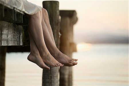 Couple legs dangling on pier, Bavaria, Germany Stock Photo - Premium Royalty-Free, Code: 6121-08361581