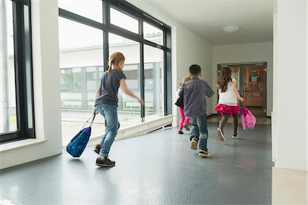 Children running with sports bags in corridor of sports hall, Munich, Bavaria, Germany Stock Photo - Premium Royalty-Free, Code: 6121-08361673