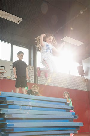 practise - Children jumping from stack of sport mats in sports hall, Munich, Bavaria, Germany Stock Photo - Premium Royalty-Free, Code: 6121-08361675