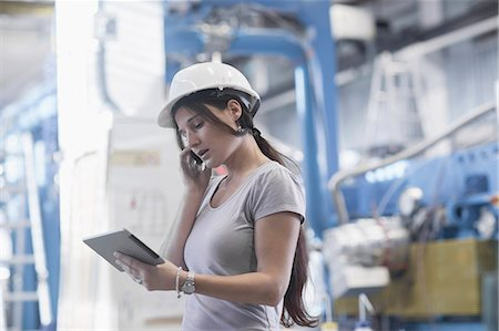 Female engineer using a digital tablet and mobile phone in an industrial plant, Freiburg Im Breisgau, Baden-Württemberg, Germany Stock Photo - Premium Royalty-Free, Code: 6121-08361694
