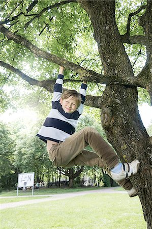 Boy climbing on tree and smiling, Munich, Bavaria, Germany Stock Photo - Premium Royalty-Free, Code: 6121-08361620