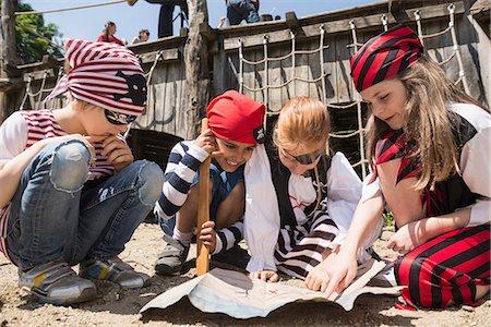 Girls examining a treasure map in a adventure playground, Bavaria, Germany Stock Photo - Premium Royalty-Free, Code: 6121-08361624