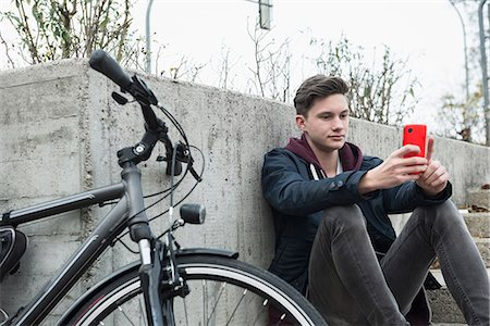 Young man text messaging on mobile phone and leaning against wall, Munich, Bavaria, Germany Stock Photo - Premium Royalty-Free, Code: 6121-08522151