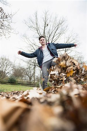 pile leaves playing - Young man kicking pile of autumn dry leaves on field, Munich, Bavaria, Germany Stock Photo - Premium Royalty-Free, Code: 6121-08522176