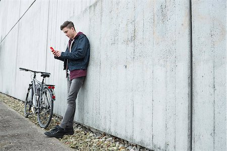 Young man text messaging on smart phone and leaning against concrete wall, Munich, Bavaria, Germany Stock Photo - Premium Royalty-Free, Code: 6121-08522179
