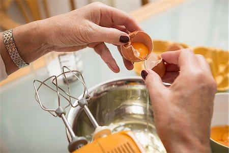 Senior woman dividing egg white and egg yolk in kitchen, Munich, Bavaria, Germany Stock Photo - Premium Royalty-Free, Code: 6121-08522185