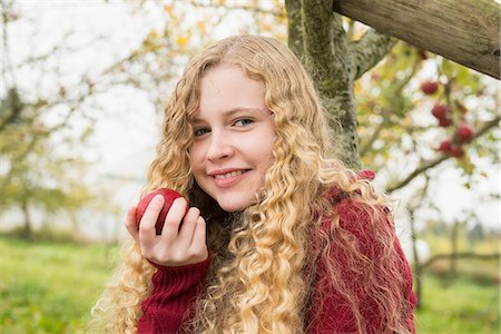 Portrait of a blond teenage girl eating an apple in an apple orchard farm, Bavaria, Germany Stock Photo - Premium Royalty-Free, Code: 6121-08522249