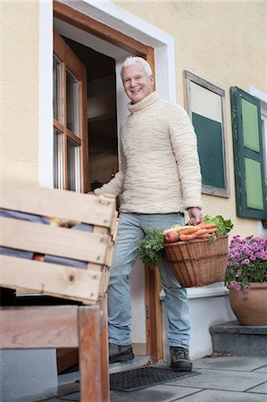 Portrait of a mature man holding basket full of vegetables in wholefood shop and smiling, Bavaria, Germany Stock Photo - Premium Royalty-Free, Code: 6121-08522259
