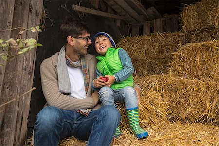 small - Father and son sitting on straw in the stable and laughing, Bavaria, Germany Stock Photo - Premium Royalty-Free, Code: 6121-08522270