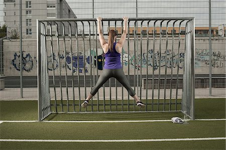 Rear view of a young woman doing chin-ups on football ground, Bavaria, Germany Stock Photo - Premium Royalty-Free, Code: 6121-08522205