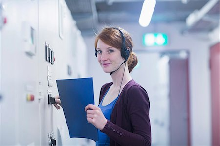 Portrait of a young female engineer wearing headset and controlling a switchgear in control room, Freiburg im Breisgau, Baden-Württemberg, Germany Stock Photo - Premium Royalty-Free, Code: 6121-08522354