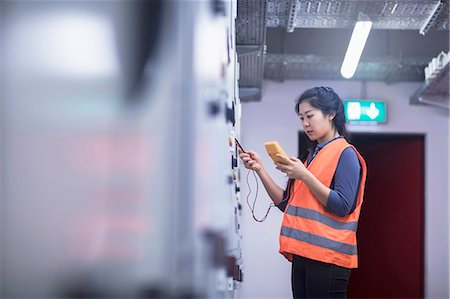 east asian - Young female engineer examining control panel with multimeter in an industrial plant, Freiburg im Breisgau, Baden-Württemberg, Germany Stock Photo - Premium Royalty-Free, Code: 6121-08522408