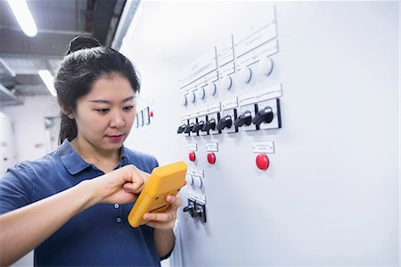 east asian - Young female engineer examining control panel with multimeter in an industrial plant, Freiburg im Breisgau, Baden-Württemberg, Germany Stock Photo - Premium Royalty-Free, Code: 6121-08522413