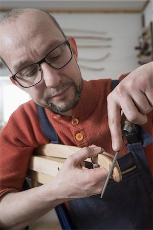 Male bow maker files the tips of a bow in workshop, Bavaria, Germany Stock Photo - Premium Royalty-Free, Code: 6121-08660289