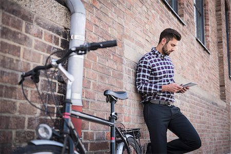 Young man using digital tablet and leaning against brick wall, Munich, Bavaria, Germany Stock Photo - Premium Royalty-Free, Code: 6121-08858998