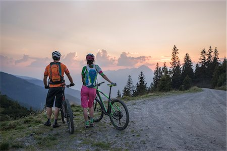 Rear view of young couple of mountain bikers standing in the alpine landscape and looking at view during sunset, Zillertal, Tyrol, Austria Stock Photo - Premium Royalty-Free, Code: 6121-08859079