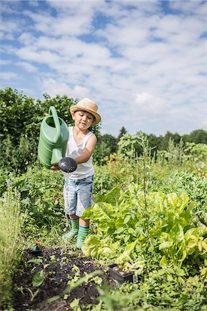 Little boy watering seedling in a community garden, Bavaria, Germany Stock Photo - Premium Royalty-Free, Code: 6121-08859037