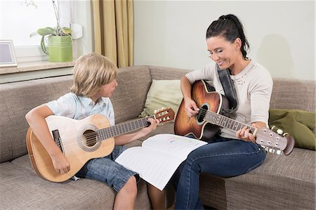 Woman with her son playing guitar in living room, Bavaria, Germany Stock Photo - Premium Royalty-Free, Code: 6121-08859184