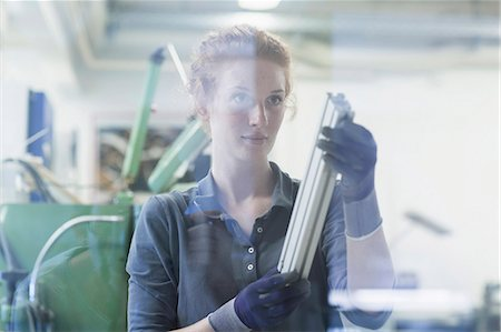 Young female engineer looking at machine part in an industrial plant, Freiburg im Breisgau, Baden-Württemberg, Germany Stock Photo - Premium Royalty-Free, Code: 6121-08859279