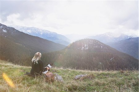 Young woman sitting with dog in the mountain, Bavaria, Germany Stock Photo - Premium Royalty-Free, Code: 6121-08859358