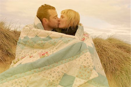 Couple kissing under blanket on beach Stock Photo - Premium Royalty-Free, Code: 6122-07692369