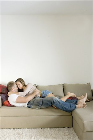 Young couple lying on sofa and embracing Stock Photo - Premium Royalty-Free, Code: 6122-07692567