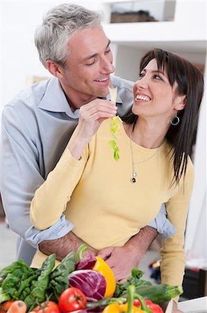 Happy couple eating fresh vegetables Stock Photo - Premium Royalty-Free, Code: 6122-07693672