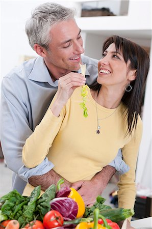 Happy couple eating fresh vegetables Stock Photo - Premium Royalty-Free, Code: 6122-07693672