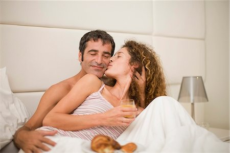 Smiling couple having breakfast in bed Stock Photo - Premium Royalty-Free, Code: 6122-07694003